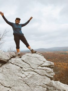 Maria with her hands in the air on top of a rock