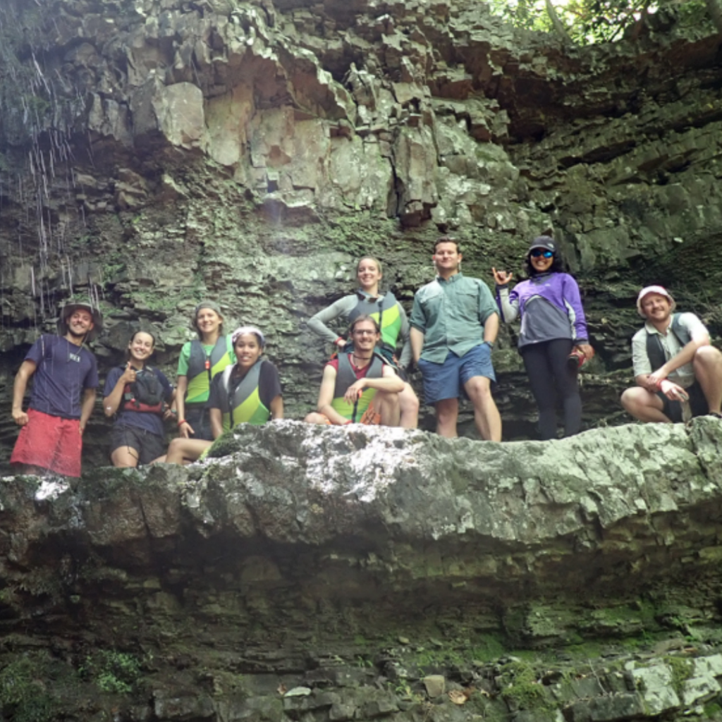 Crew of apprentices stand together in a small cave.